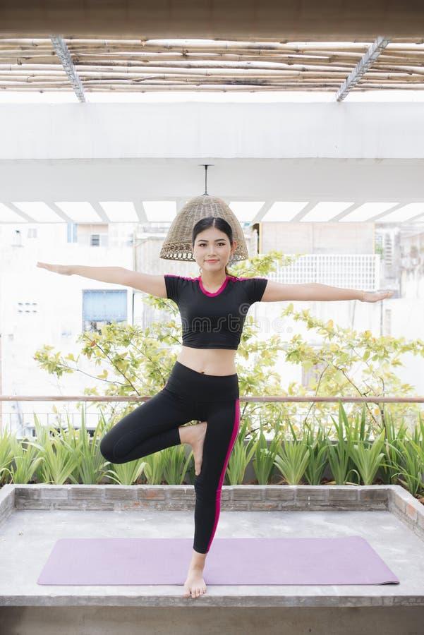 Ung asiatisk kvinna i avkoppling som sträcker position på hennes balkonggolv fotografering för bildbyråer