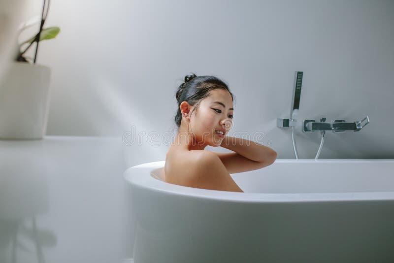 Ung asiatisk kvinna i badkar fotografering för bildbyråer