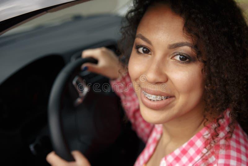 Ung asiatisk kvinna i bil Den moderna ung flickachauffören kör en bil och ser bort med ett leende med hänglsen royaltyfri foto