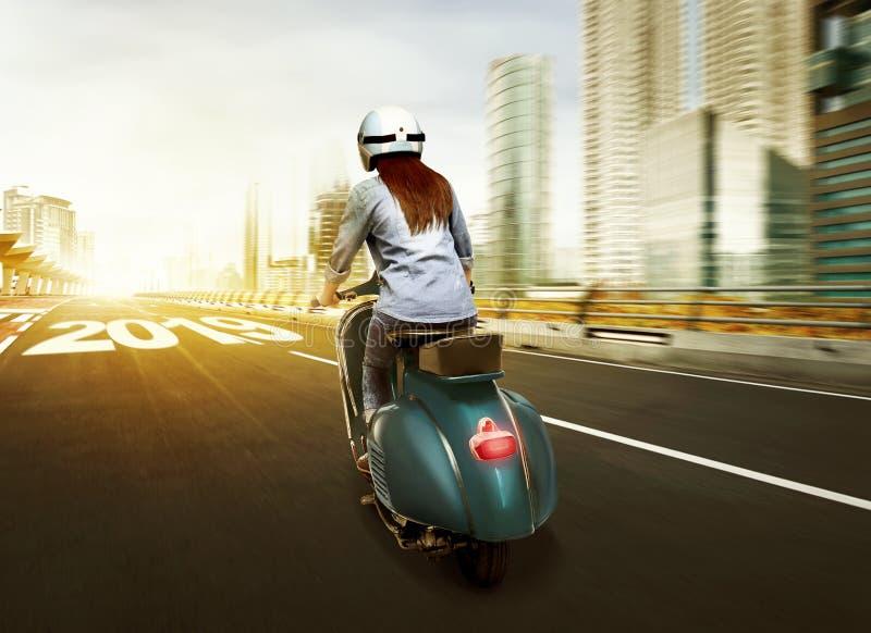 Ung asiatisk kvinna i hjälm som rider en sparkcykel på staden med 20 arkivbild
