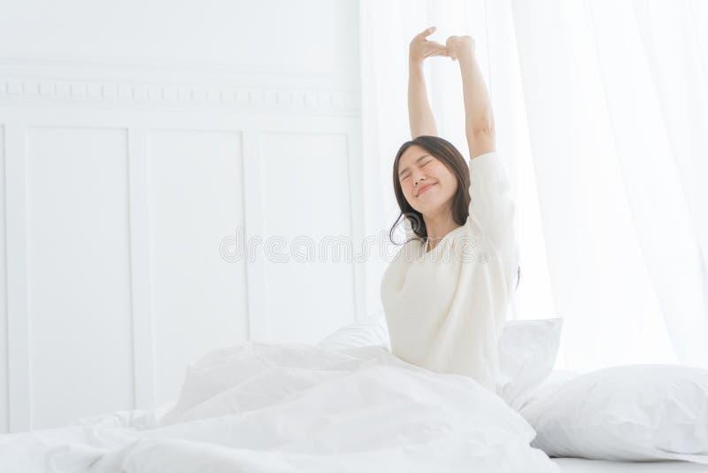 Ung asiatisk kvinna i morgonen henne som sträcker i hennes säng i sovrummet royaltyfri fotografi