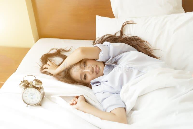 Ung asiatisk kvinna i säng som försöker att vakna upp med ringklockan royaltyfri foto