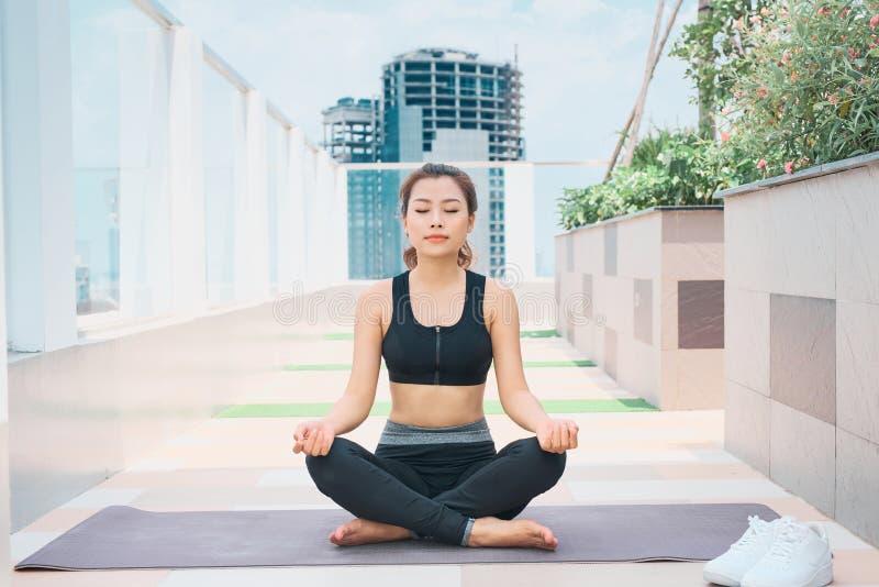 Ung asiatisk kvinna i sportkläder som utomhus gör sportar fotografering för bildbyråer