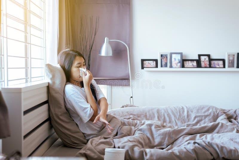 Ung asiatisk kvinna med att blåsa för förkylning och rinnande näsa på säng, sjukt kvinnligt nysa, begrepp av hälsa fotografering för bildbyråer