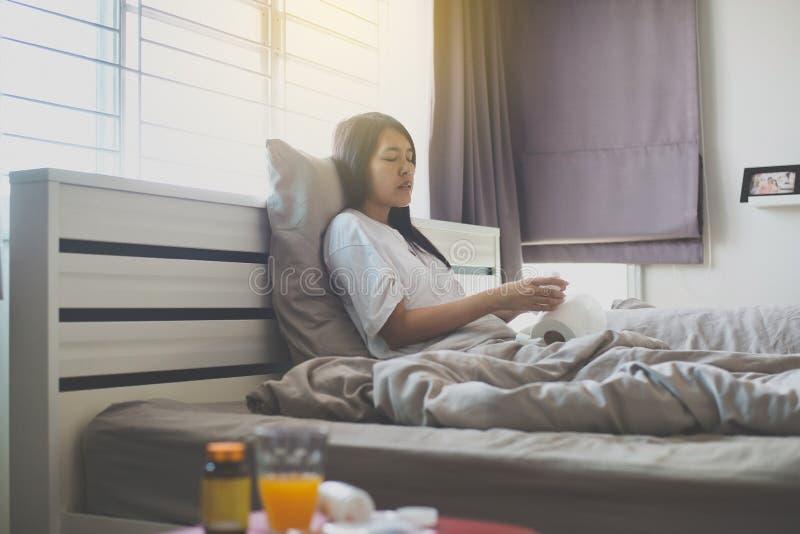 Ung asiatisk kvinna med att blåsa för förkylning och rinnande näsa på säng, sjukt nysa för kvinna royaltyfri fotografi