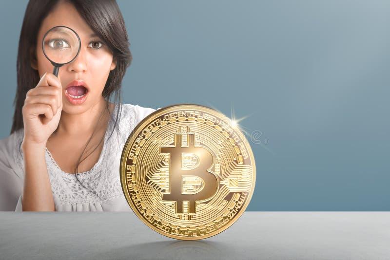 Ung asiatisk kvinna med förstoringsapparaten som ser guld- bitcoin arkivbild