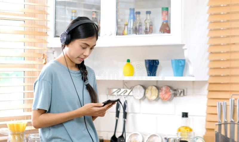 Ung asiatisk kvinna med hörlurar som lyssnar till musik från hemmastadd kökbakgrund för mobiltelefon, folk och teknologilivsstil fotografering för bildbyråer