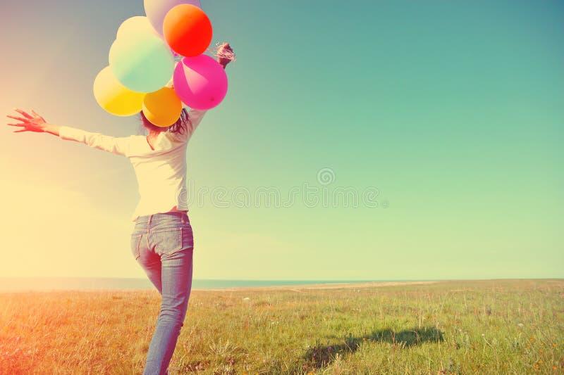 Ung asiatisk kvinna med kulöra ballonger arkivfoton