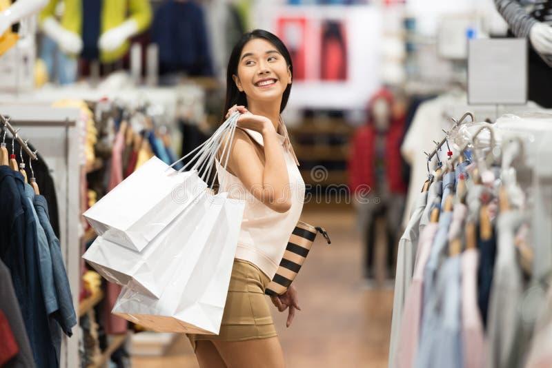 Ung asiatisk kvinna med shoppingpåsar i det lyxiga klädlagret royaltyfri foto