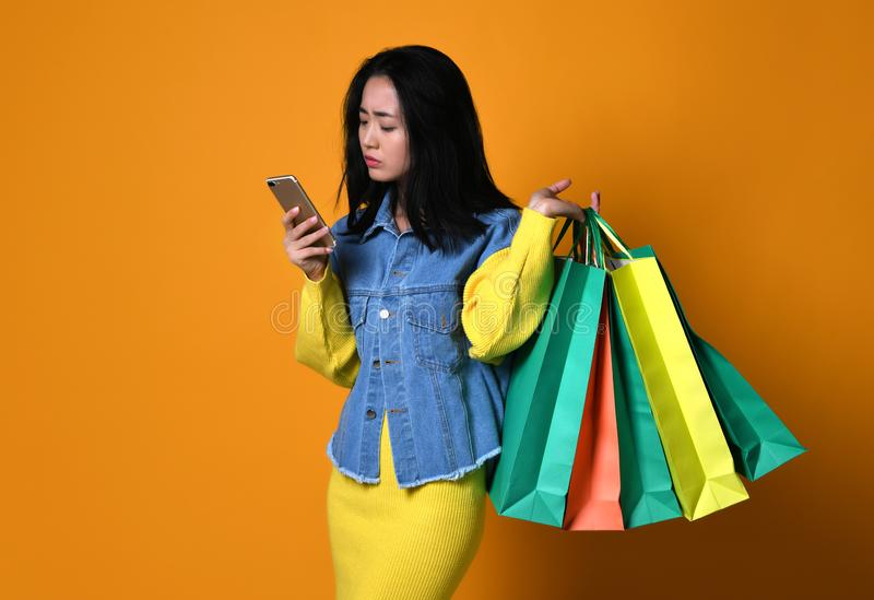 Ung asiatisk kvinna med shoppingpåsar på färgbakgrund royaltyfri foto