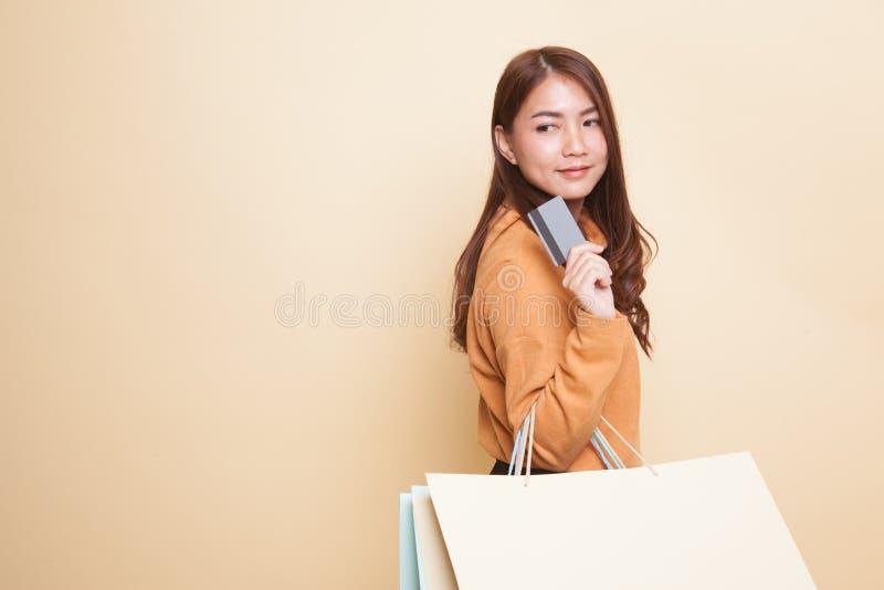 Ung asiatisk kvinna med shoppingpåsen och det tomma kortet arkivbilder