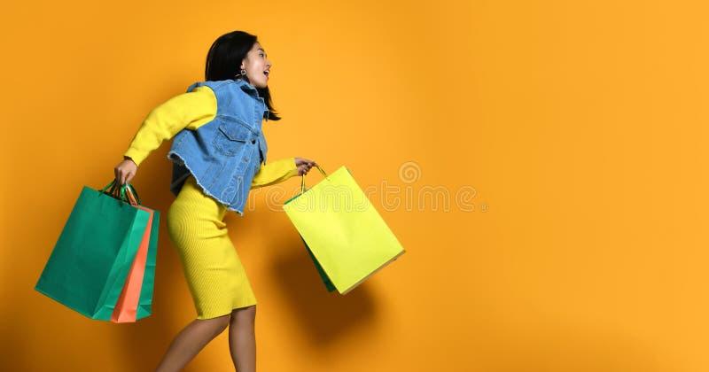 Ung asiatisk kvinna med shoppingp?sar p? f?rgbakgrund arkivfoto