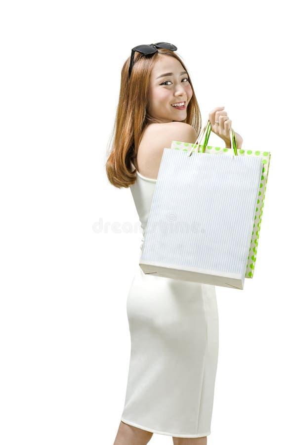 Ung asiatisk kvinna med solglasögon och att stå för shoppingpåsar arkivbilder