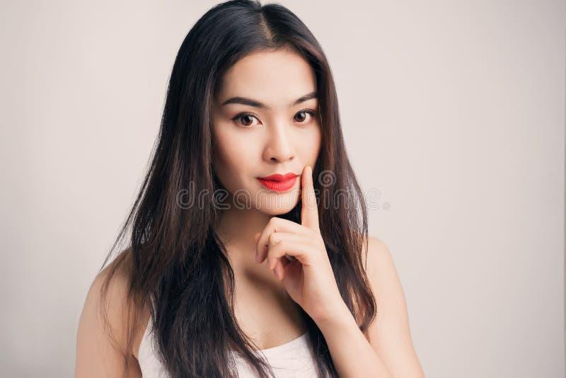 Ung asiatisk kvinna med tvivelaktigt sinnesrörelse royaltyfri fotografi