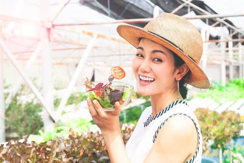 Ung asiatisk kvinna som äter veggiesallad med hydrokulturlantgården i bakgrund arkivfoto