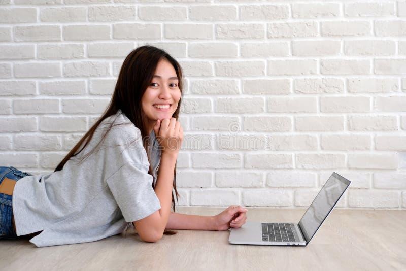 Ung asiatisk kvinna som använder bärbar datordatoren som är främst av vit bakgrund för tegelstenvägg med kopieringsutrymme, folk  royaltyfria foton