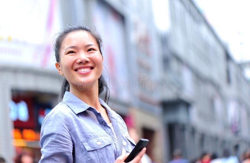 Ung asiatisk kvinna som använder den smarta telefonen på shoppinggatan fotografering för bildbyråer