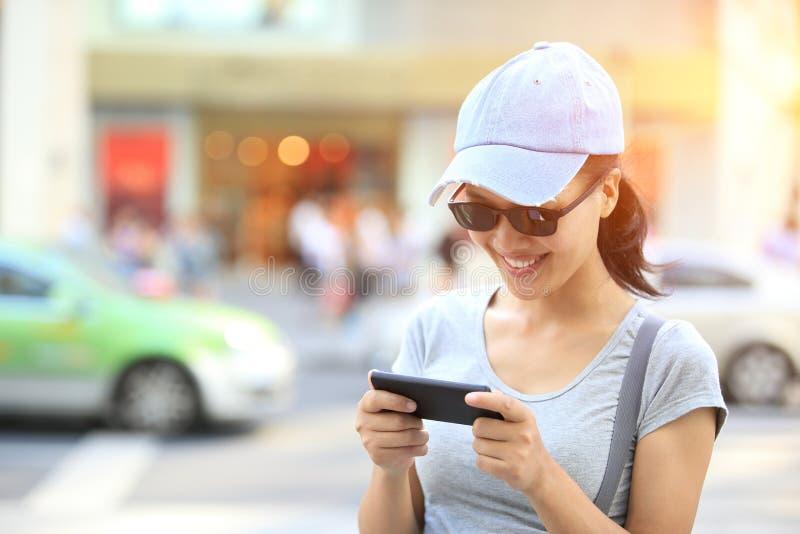 Ung asiatisk kvinna som använder hennes utomhus- smarta telefon fotografering för bildbyråer
