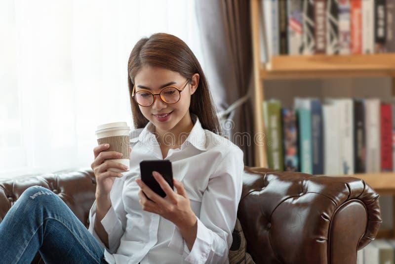 Ung asiatisk kvinna som använder mobiltelefonen och rymmer en varm lycklig och avslappnande tid för kopp kaffe, arkivfoton