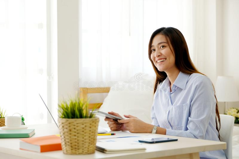 Ung asiatisk kvinna som arbetar med det hemmastadda kontoret för digital minnestavla med lycklig sinnesrörelse som hemifrån arbet royaltyfria foton