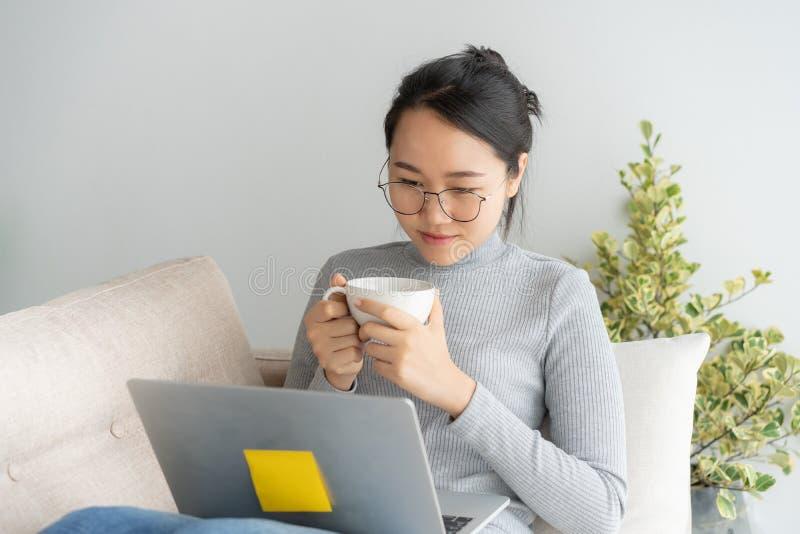 Ung asiatisk kvinna som arbetar på bärbara datorn i inrikesdepartementetskrivbordet och tycka om koppen kaffe royaltyfria foton