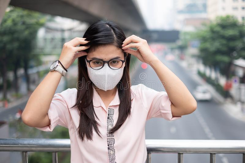 Ung asiatisk kvinna som bär den respiratoriska maskeringen N95 för att skydda och filtrera pm2 som består av partiklar fråga 5 mo arkivfoton