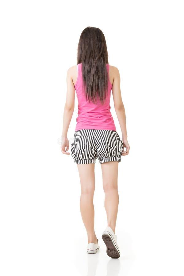 Ung asiatisk kvinna som går, skott från en baksida royaltyfri foto