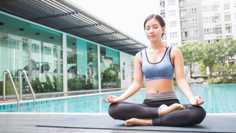 Ung asiatisk kvinna som gör yogaflyttningar eller mediterar vid pölen, royaltyfri foto