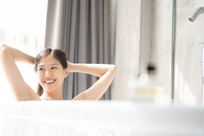 Ung asiatisk kvinna som kopplar av i ett bad arkivbild