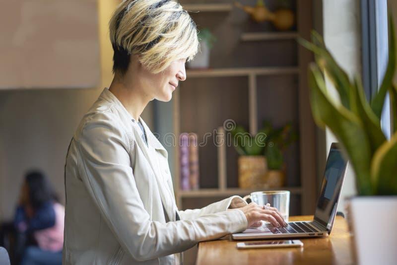 Ung asiatisk kvinna som ler genom att använda den smarta telefonen och bärbara datorn på coffee shop arkivfoton