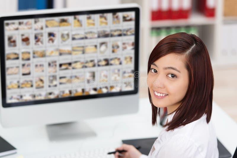 Ung asiatisk kvinna som redigerar fotografier royaltyfri foto