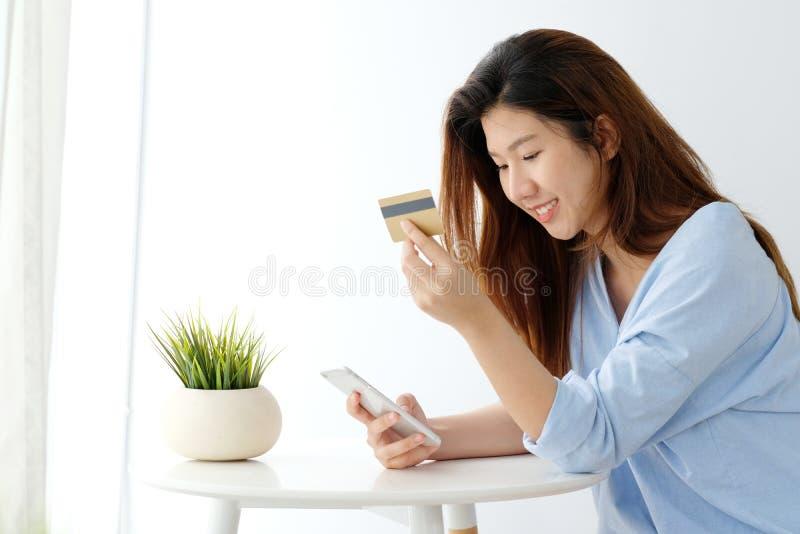 Ung asiatisk kvinna som rymmer kreditkorten och använder den smarta telefonen för att shoppa online-, affärs- och teknologibegrep arkivbild