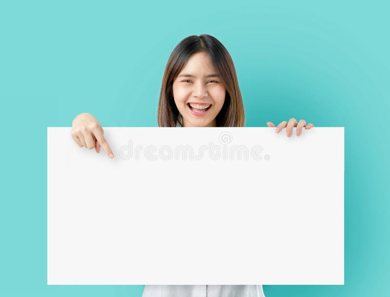 Ung asiatisk kvinna som rymmer tomt papper med att le framsidan och att se på den blåa bakgrunden för annonsering av tecken arkivfoton