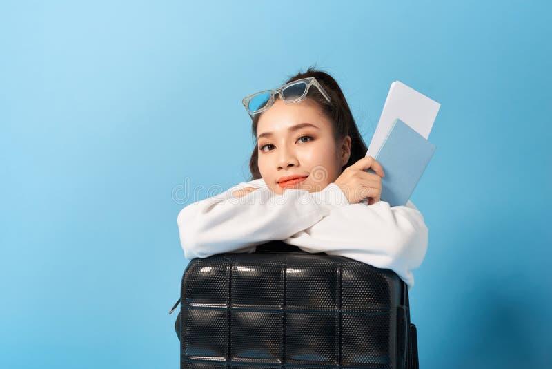 Ung asiatisk kvinna som sitter nära ett resväskainnehavpass på en blå bakgrund arkivfoton
