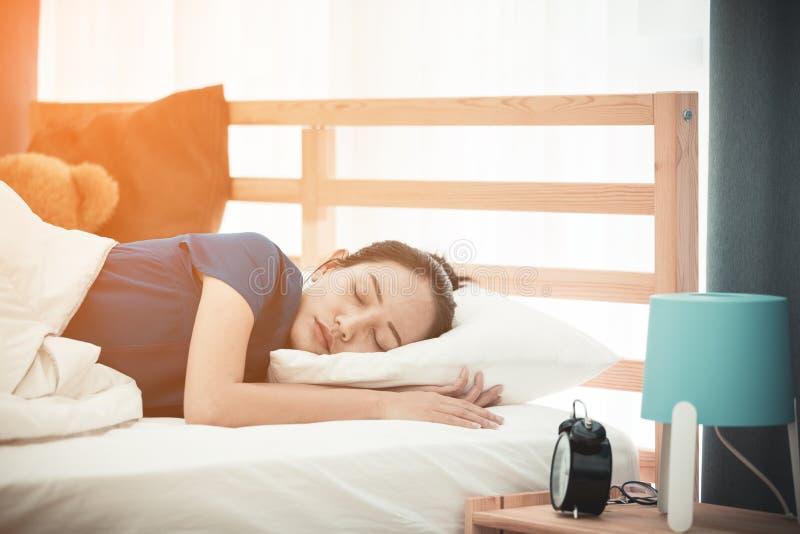 Ung asiatisk kvinna som sover i säng, royaltyfri foto