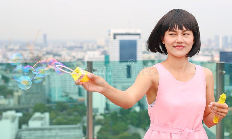 Ung asiatisk kvinna som spelar bubblan på taköverkanten av byggnad royaltyfri bild