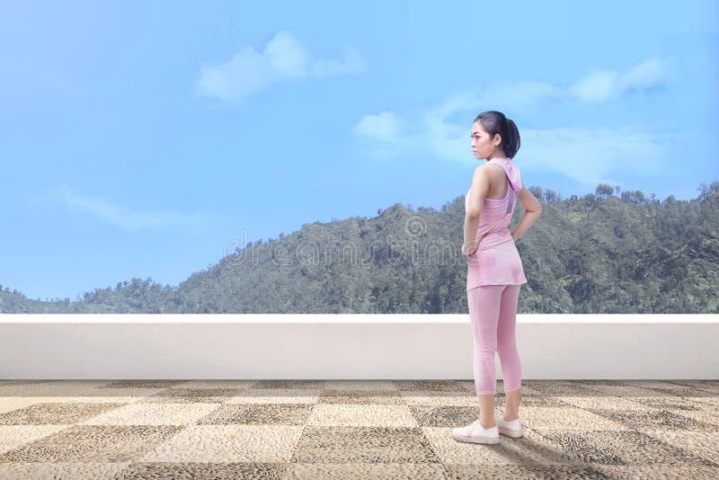 Ung asiatisk kvinna som tar ett avbrott, når att ha kört som är utomhus- royaltyfria foton
