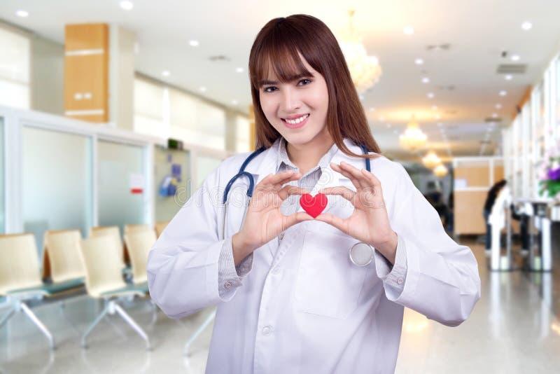Ung asiatisk kvinnadoktor som rymmer en röd hjärta som står på sjukhusbakgrund Sunt omsorgbegrepp royaltyfria bilder