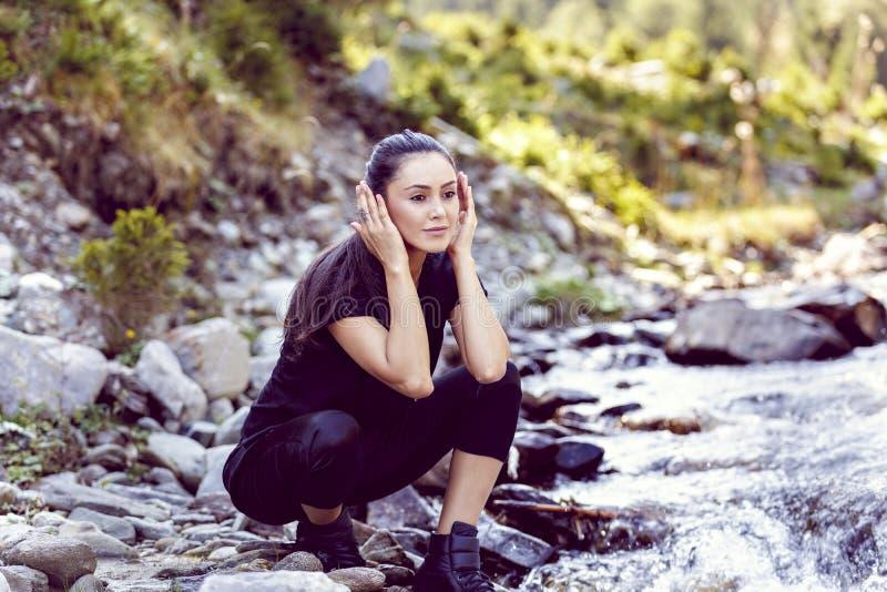 Ung asiatisk kvinnafotvandrare vid floden royaltyfria foton
