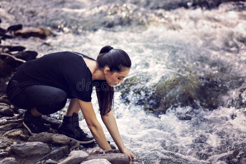 Ung asiatisk kvinnafotvandrare vid floden royaltyfri foto
