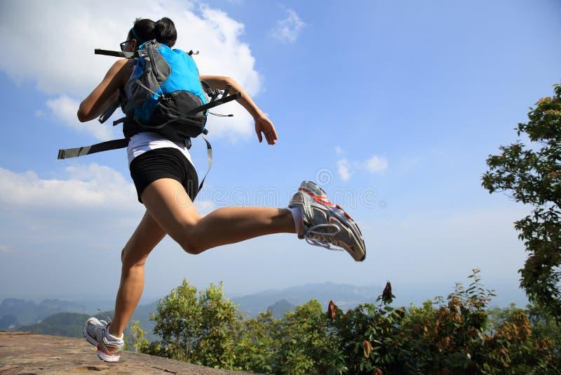 Ung asiatisk kvinnafotvandrarespring på bergmaximum arkivbilder