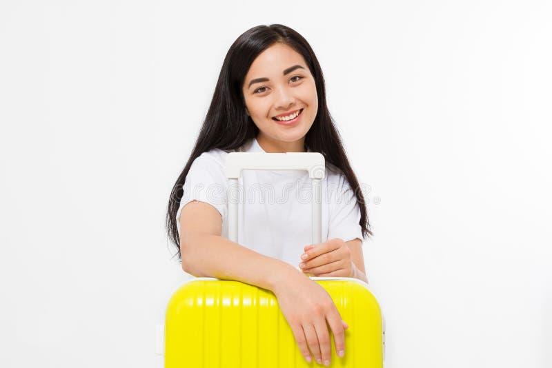 Ung asiatisk kvinnahandelsresande med den gula resväskan som isoleras på vit bakgrund kopiera avstånd Sommarloppferier royaltyfri foto