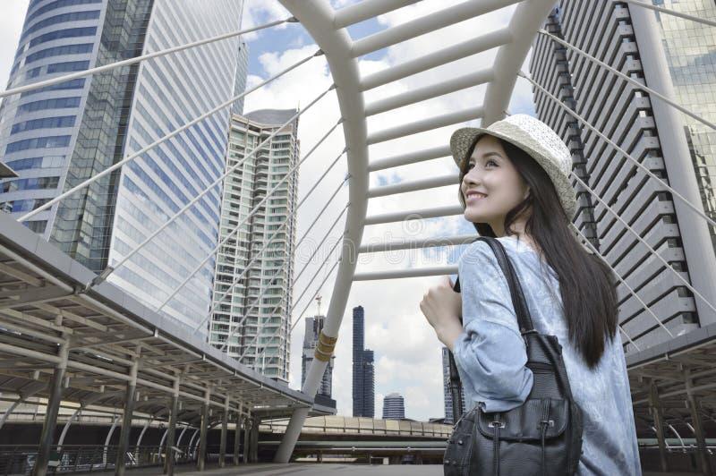 Ung asiatisk kvinnahandelsresande med en ryggsäck på hennes skuldra som går på banabron över modernt stadstorn i Bangkok, Thailan royaltyfri bild