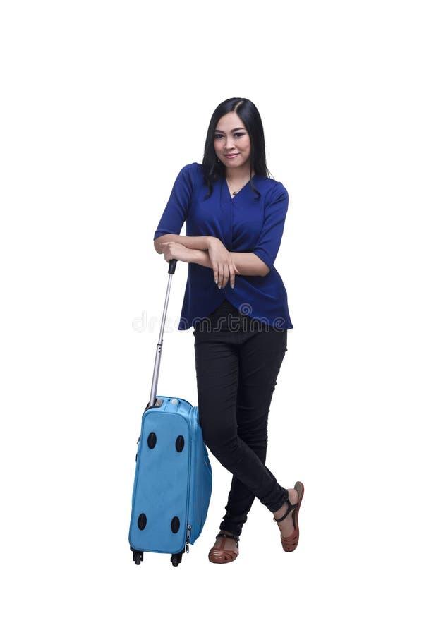 Ung asiatisk kvinnahandelsresande som poserar bredvid en resväska arkivfoto