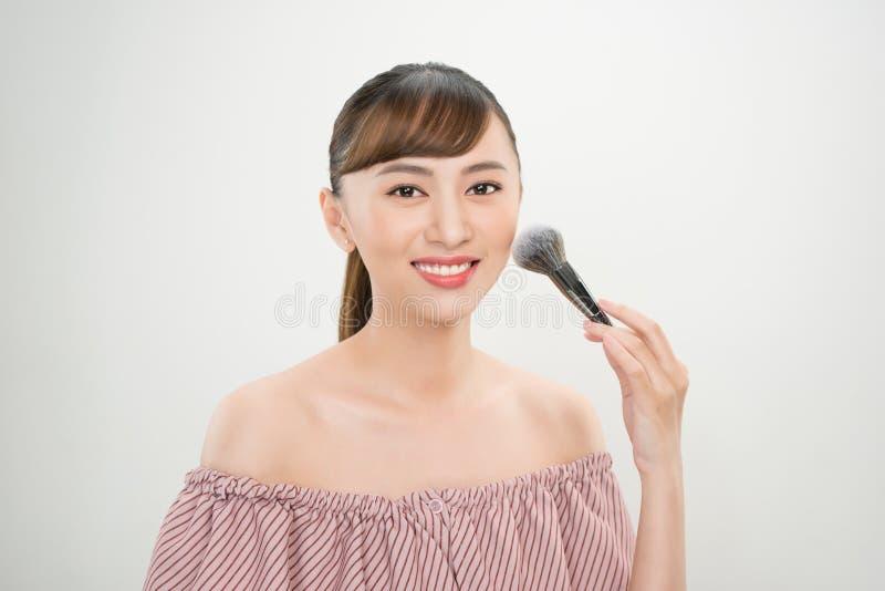 Ung asiatisk kvinnamakeupborste Fors f?r smink- och sk?nhetbehandlingbegrepp arkivbilder