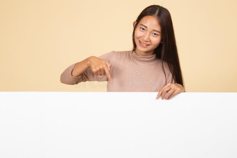 Ung asiatisk kvinnapunkt till ett tomt tecken arkivfoto
