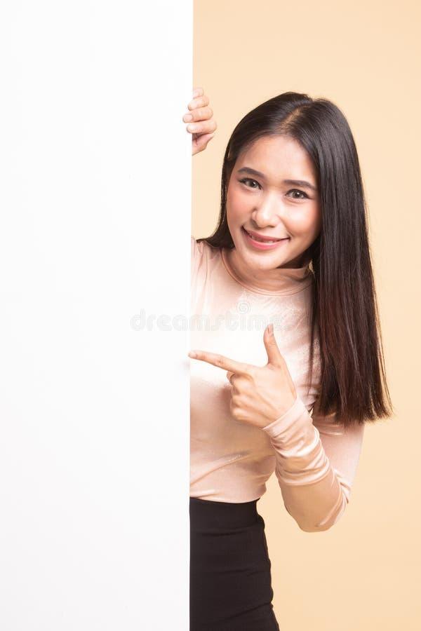 Ung asiatisk kvinnapunkt till ett tomt tecken fotografering för bildbyråer