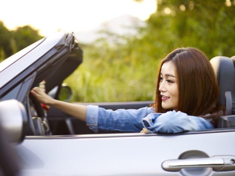Ung asiatisk kvinnaridning i en konvertibel bil royaltyfria foton