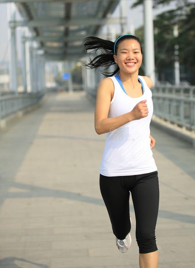 Ung asiatisk kvinnaspring på den moderna stadsspången royaltyfria foton