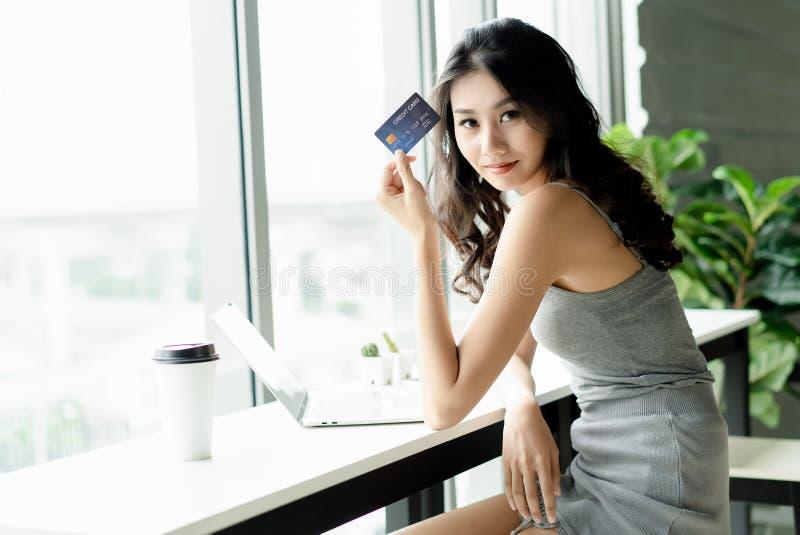 Ung asiatisk kvinnavisningkreditkort till kameran, medan arbeta wi arkivbilder